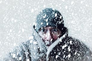 man in hat and winter coat in snow storm