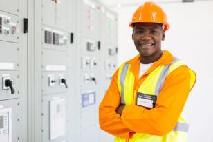 man in safety-wear in front of electrical panel